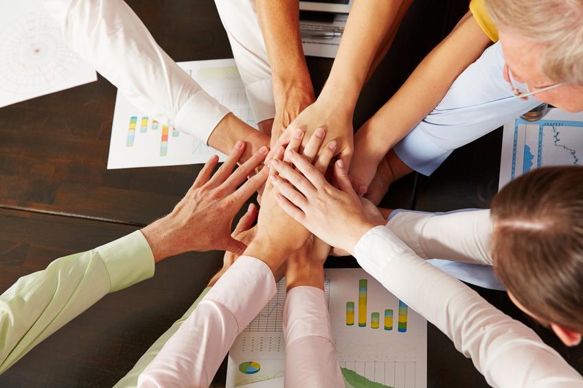 Viele gestapelte Hände von oben als Zeichen der Zusammenarbeit im Büro